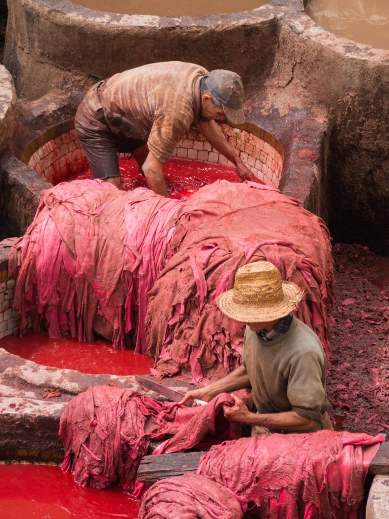 two men working in textile dying factory. Bondage labor is rampant in the textile industry,