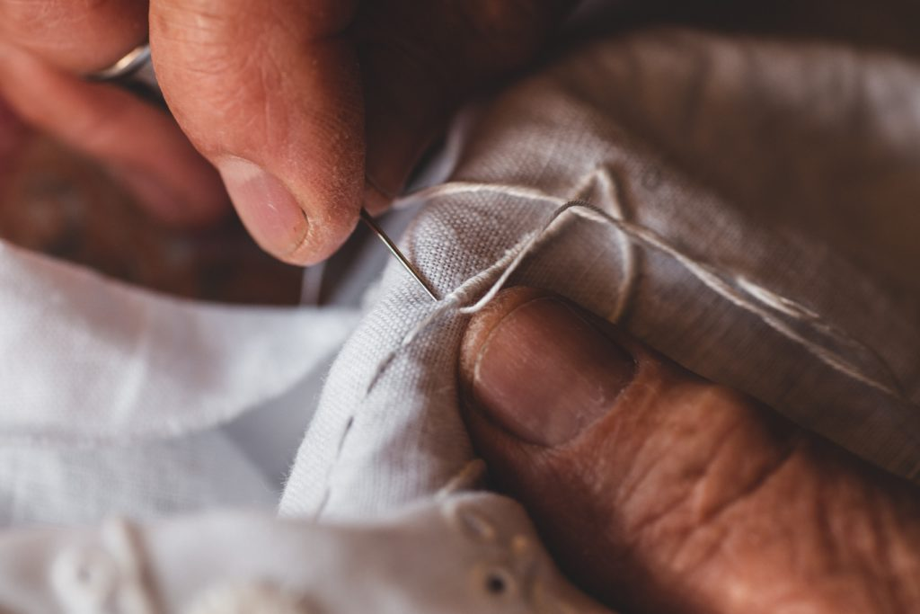 close up of embroidery with white thread. Bondage labor is rampant in the textile industry.