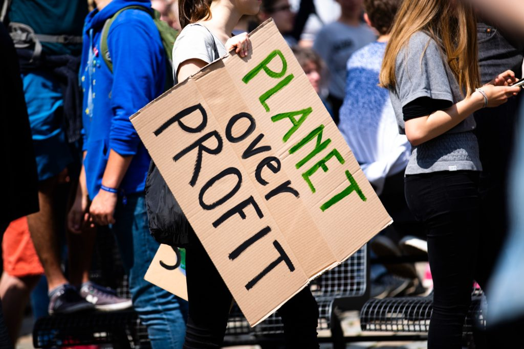 Climate Change Strike sign that reads planet over profit - interview between Rocco Ciciretti and Cait Bagby about the Viability of ESG Ratings